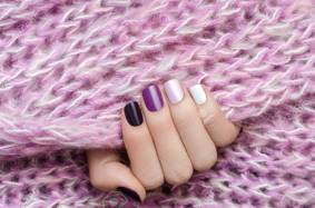 Piurple nail design. Beautiful female hand with different shades of purple manicure